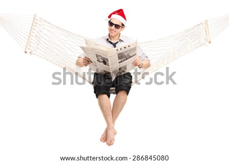 Young guy with Santa hat sitting in a hammock and reading a newspaper. The photos used in the newspaper in my copyright, you can check from the Model release that I am uploading additionally. - stock photo