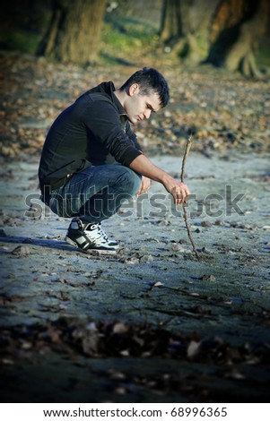 young guy write in the sand