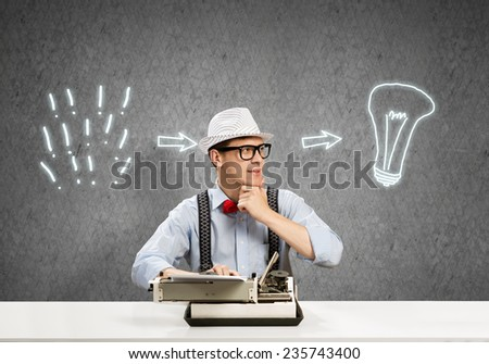 Young guy writer in hat and glasses using typing machine - stock photo