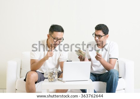 Young guys counting cash with partner, earning money from their successful online business. Asian men working from home. - stock photo