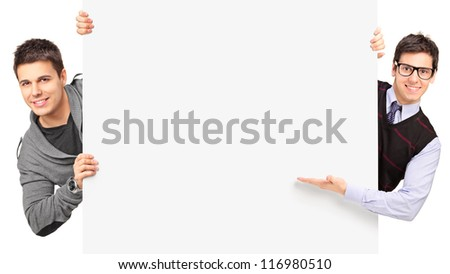 Young guys posing behind a blank panel isolated on white background