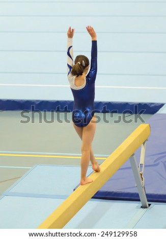 Young gymnast girl performing a choreographed routine on balance beam in an indoor competition. - stock photo