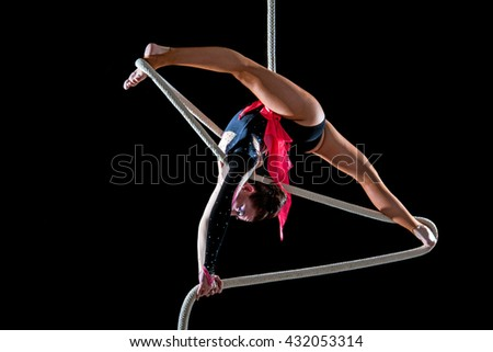 Young gymnast hanging on a rope. The show of acrobats