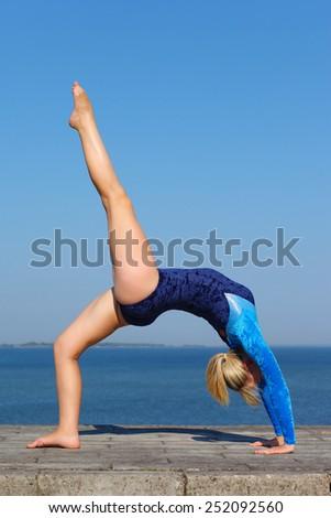 Young gymnast on seashore - stock photo