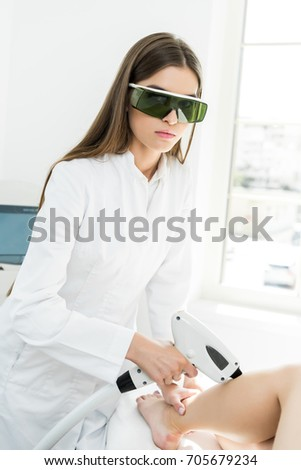 young hair removal therapist in coat with laser epilator looking at camera
