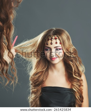 Young hairdresser giving  new hair style to female teen customer.  - stock photo