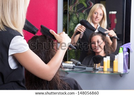 young hairstylist makes hairstyle for beautiful girl in barbershop - stock photo