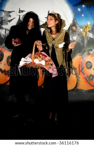 Young Halloween couple, female witch and man with sinister costume, basket with sweets.    Studio shot, graffiti  background.