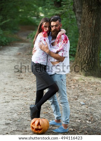 young halloween couple of bearded man with beard and sexy pretty girl with red blood and traditional autumn holiday symbol of orange spooky pumpkin outdoor in deep green forest or wood