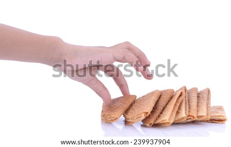 young hand take a Kuih Kapit or the Malaysian Chinese Love Letter biscuit over white background