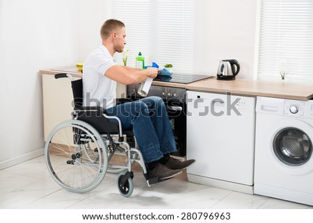 Young Handicapped Man On Wheelchair Cleaning Induction Stove