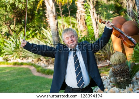 Young handicapped musician raising arms with violin outdoors. - stock photo