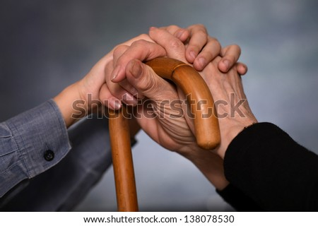 young hands holding hands grandmother on a gray background - stock photo