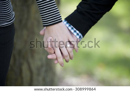 Young hands holding with an engagement ring on a sunny day. - stock photo