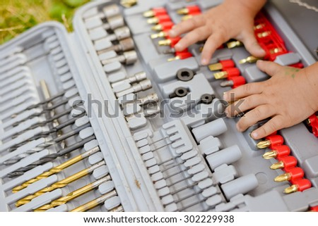 Young hands on drill bits. Closeup picture - stock photo