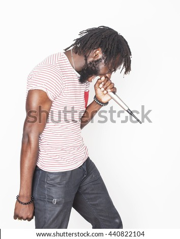 young handsome african american boy singing emotional with microphone isolated on white background, in motion gesturing smiling