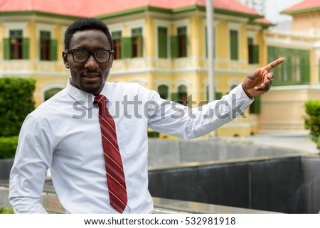 Young handsome African businessman pointing finger