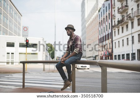 young handsome afro black man sitting on a handrail outside in the city, looking straight right, pensive - serious, thoughtful, thinking future concept - wearing jeans overalls and checked shirt - stock photo