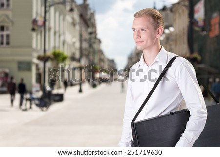 Young handsome architect with drawings folder on the street - stock photo