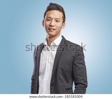 young handsome asian business man standing - stock photo