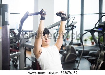 young handsome asian man works out in modern gym
