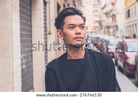 Young handsome Asian model dressed in black tunic posing in the city streets - stock photo