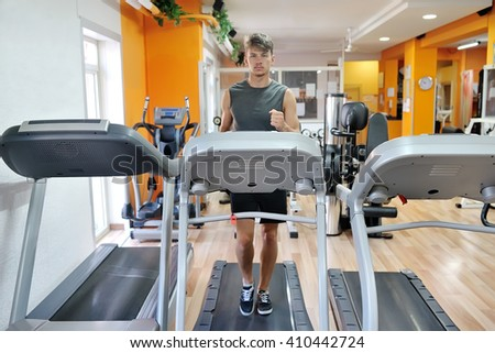 young handsome athlete running on tapis roulant in the gym - fitness wellness healthy lifestyle concept - stock photo