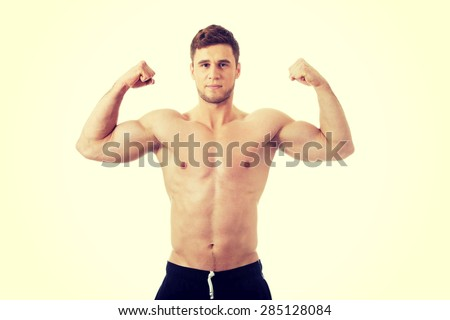 Young handsome athletic man showing his muscles.