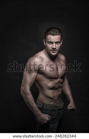 Young handsome athletic man with naked torso on dark background - stock photo