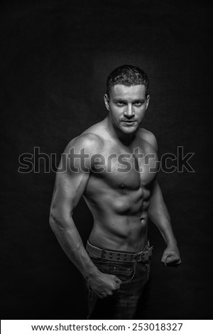Young handsome athletic man with naked torso on dark background, black and white
