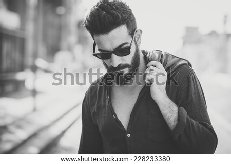 young handsome attractive bearded model man in urban context - stock photo