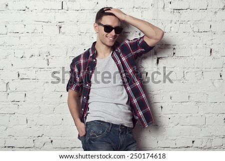 Young handsome attractive man hipster with sunglasses with his hand in the hair smiles. - stock photo