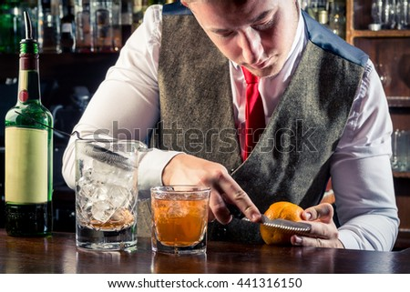 young handsome bartender decorating whisky whiskey sour cocktail bar interior bottles blurry background vest red tie