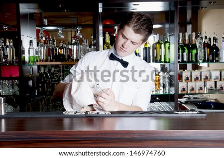 Young handsome bartender working  in front of the bar. - stock photo