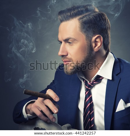 Young handsome bearded caucasian man sitting on chair with a cigar. Perfect skin and hairstyle. Wearing blue suit and watch. Studio portrait on gradient black to grey background. Toned