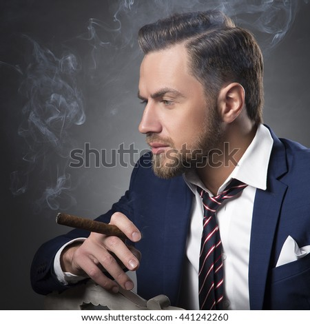 Young handsome bearded caucasian man sitting on chair with a cigar. Perfect skin and hairstyle. Wearing blue suit and watch. Studio portrait on gradient black to grey background.