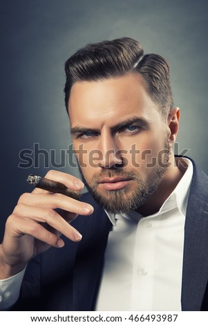 Young handsome bearded caucasian man sitting on chair with a cigar. Perfect skin and hairstyle. Wearing grey suit. Studio portrait on gradient black to grey background. Toned