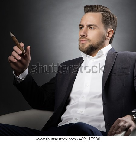 Young handsome bearded caucasian man sitting on chair with a cigar. Perfect skin and hairstyle. Wearing grey suit and watch. Studio portrait on gradient black to grey background.