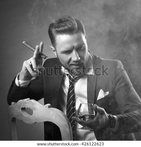 Young handsome bearded caucasian man sitting on chair with cognac and a cigar. Perfect skin and hairstyle. Wearing suit & watch. Studio portrait on gradient black to grey background. Black and white.