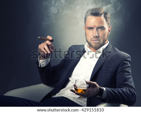 Young handsome bearded caucasian man sitting on chair with cognac and a cigar. Perfect skin and hairstyle. Wearing grey suit and watch. Studio portrait on gradient black to grey background. Toned - stock photo