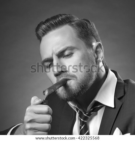 Young handsome bearded caucasian man sitting on chair with cognac and fire a cigar. Perfect skin and hairstyle. Wearing suit. Studio portrait on gradient black to grey background. Black and white