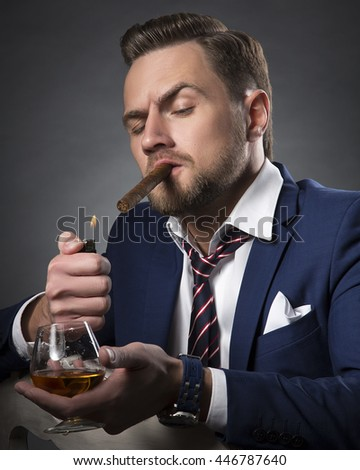 Young handsome bearded caucasian man sitting on chair with cognac and fire a cigar. Perfect skin and hairstyle. Wearing blue suit and watch. Studio portrait on gradient black to grey background.