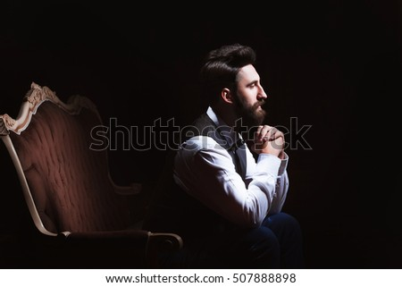 Young handsome bearded caucasian man sitting on vintage sofa. Perfect skin and hairstyle. Wearing vest, white shirt, jeans. Studio portrait with dramatic light.