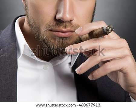 Young handsome bearded caucasian man smoking a cigar and looking straight at camera. Perfect skin and hairstyle. Wearing grey suit. Studio portrait on gradient black to grey background.
