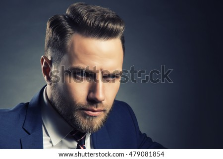 Young handsome bearded caucasian man with blue eyes sitting on chair. Perfect skin and hairstyle. Wearing blue suit. Studio portrait on gradient black to grey background. Toned