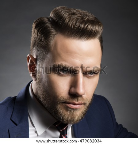 Young handsome bearded caucasian man with blue eyes sitting on chair. Perfect skin and hairstyle. Wearing blue suit. Studio portrait on gradient black to grey background.