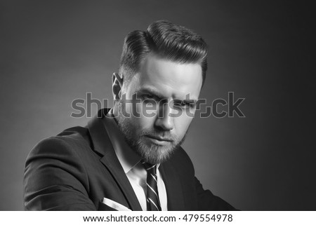 Young handsome bearded caucasian man with blue eyes sitting on chair. Perfect skin and hairstyle. Wearing blue suit and watch. Studio portrait on gradient black to grey background. Black and white