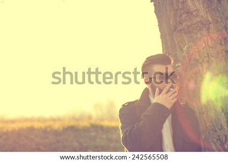 Young handsome bearded hipster man outdoors, smoking cigarette - stock photo