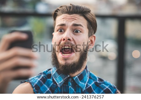 young handsome bearded hipster man selfie in the city