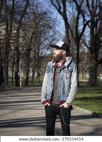 Young handsome bearded hipster man with hat in the park. - stock photo